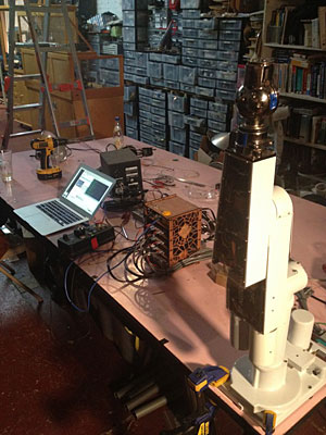 Trammell Hudson's PUMA robotic arm setup at NYC Resistor, with laptop running kinematics library, homemade controller stack, and robot.